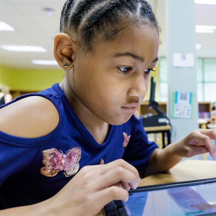An elementary magnet school student uses a tablet to creatively solve a problem.