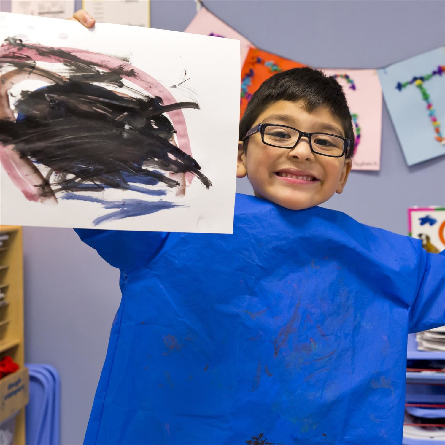 pre-k student proudly showing his art work
