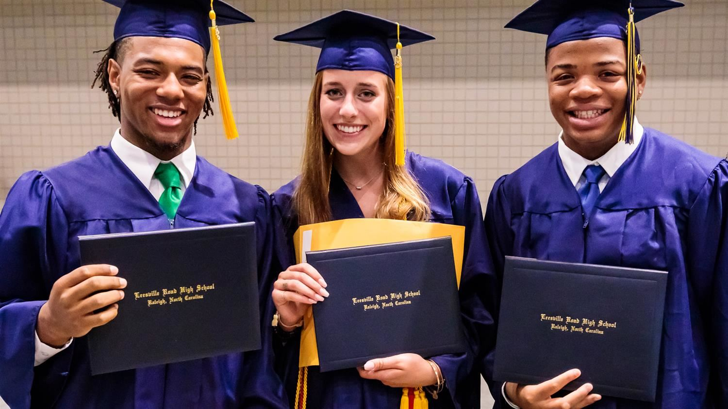 Brand new high school grads show off their diplomas