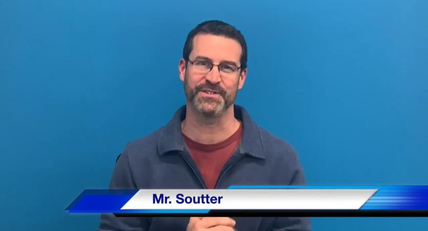 Mr. Soutter standing in front of a blue wall