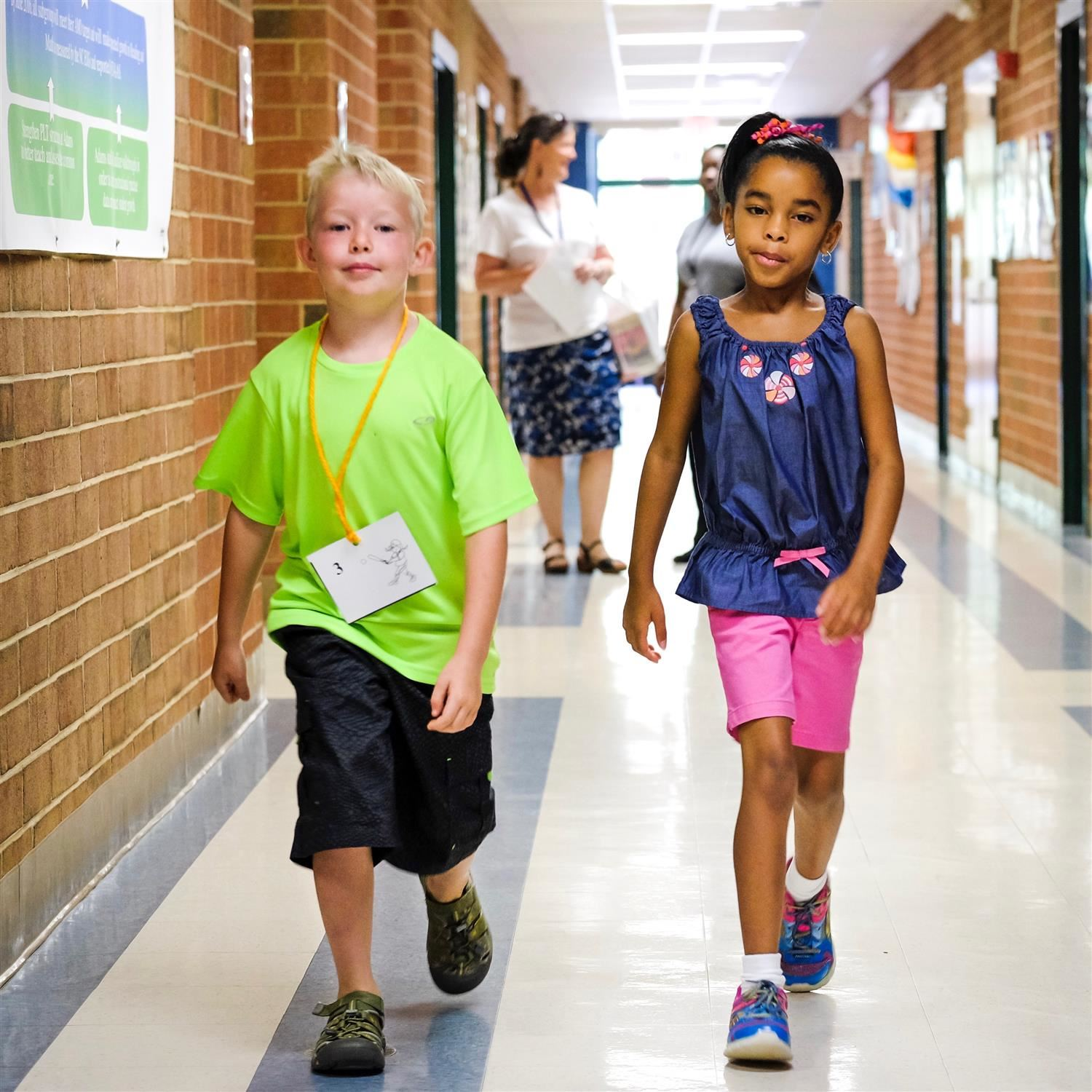 Elementary students are walking down a school hallway
