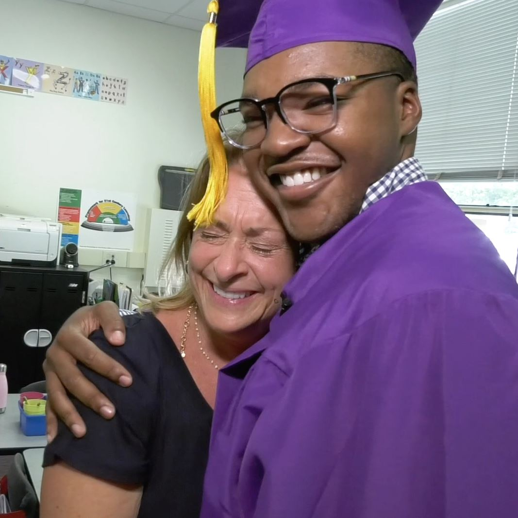Senior wearing cap and gown, hugging his former kindergarten teacher