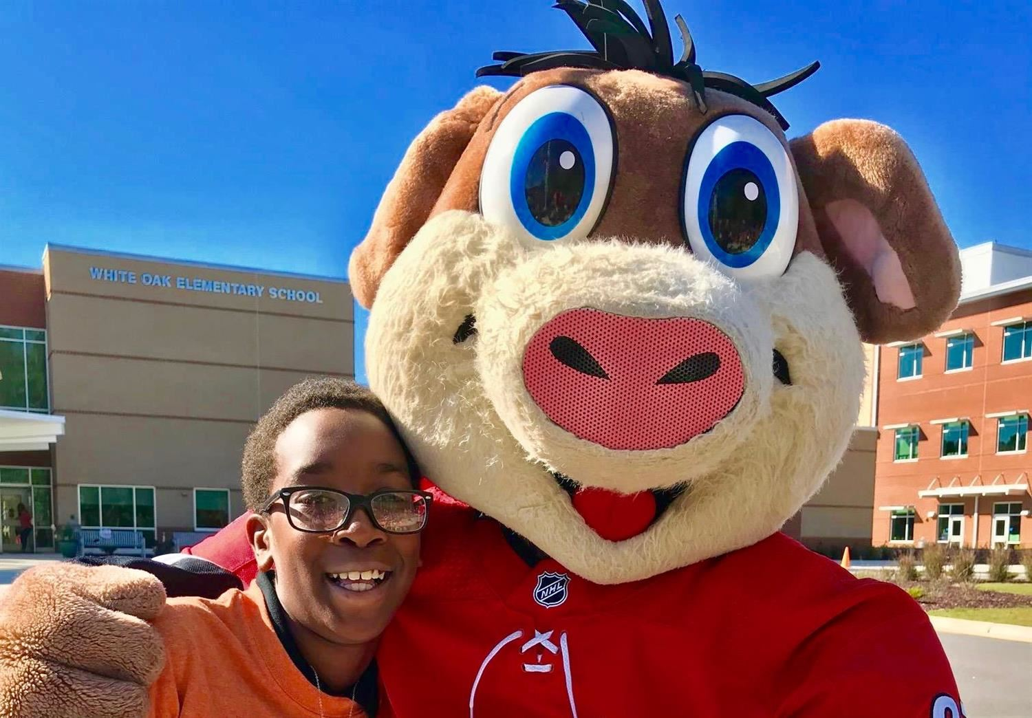 White Oak Elementary student with Hurricanes mascot Stormy