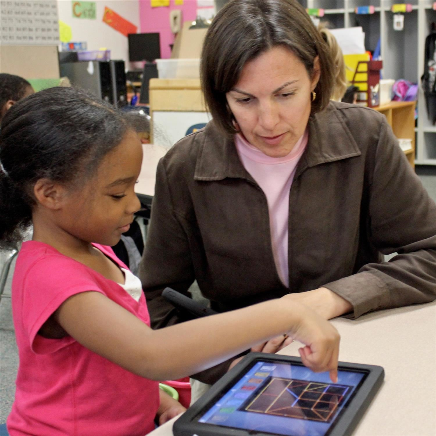 Teacher helps kindergarten student working on a portable device