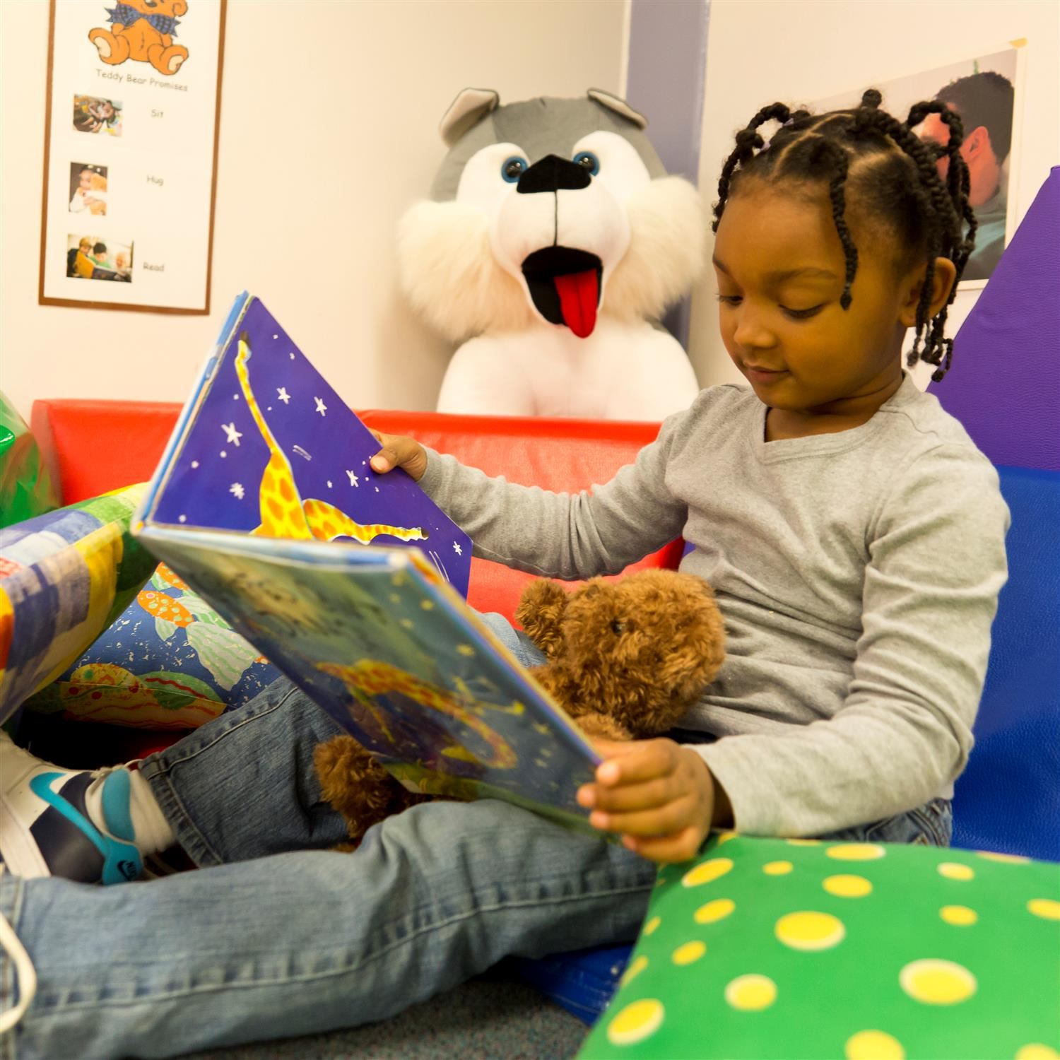 A girl in pre-kindergarten sitting on the floor reading and holding a stuffed animal.