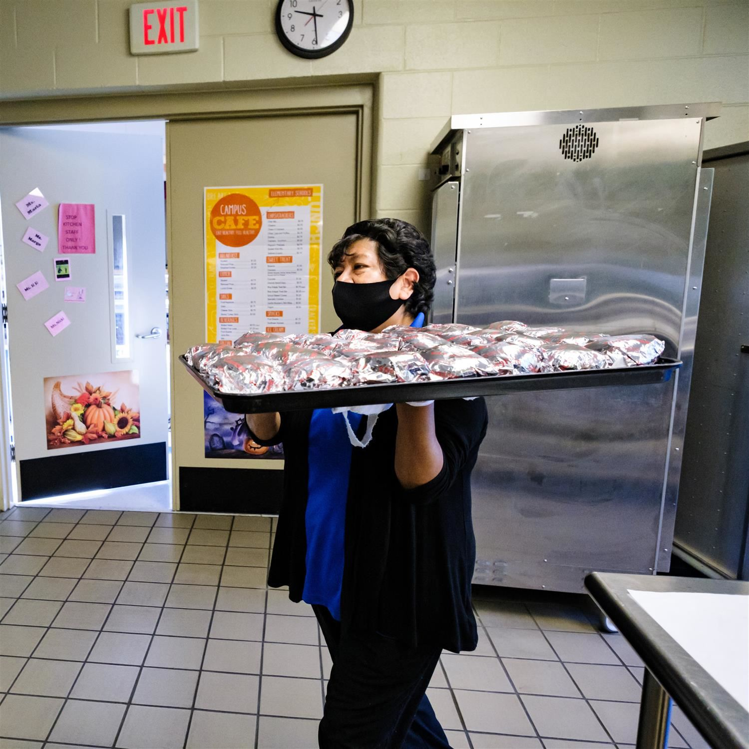 photo of cafeteria staff member carrying a tray of burgers