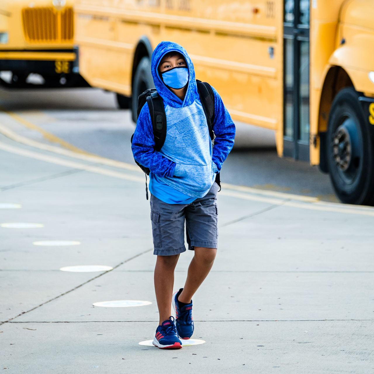 boy wearing a face covering walking away from a bus