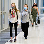 2 girls wearing masks and walking down a hallway