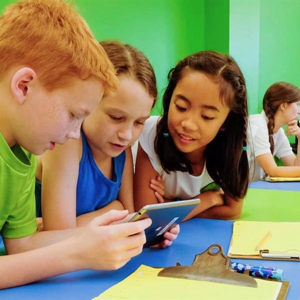 Elementary school students work together on a tablet.