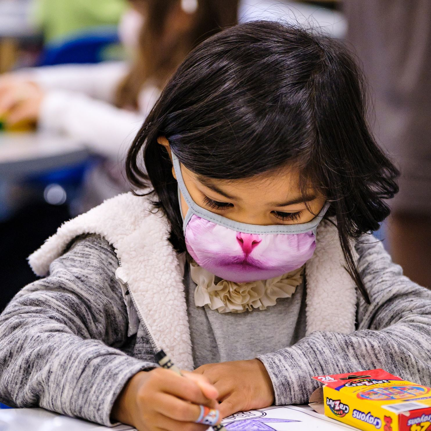 student wearing a face covering and coloring