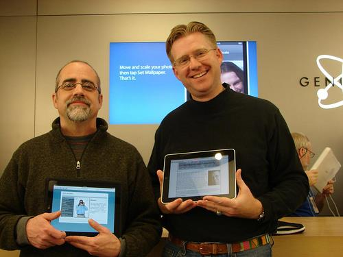 Two men showing ipads