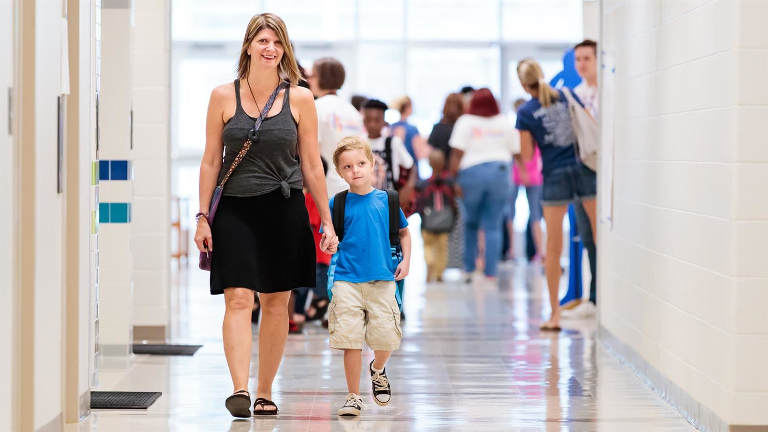 A prospective WCPSS parent is walking with her son during a school visit.