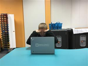 picture of young boy at a laptop making eye glasses with his hands