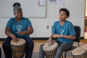 2 students playing African Drums