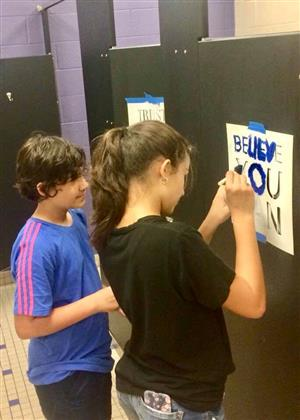 students painting with stencils