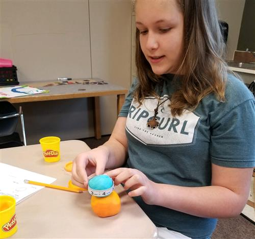 Girl measuring circumference with Play-doh spheres