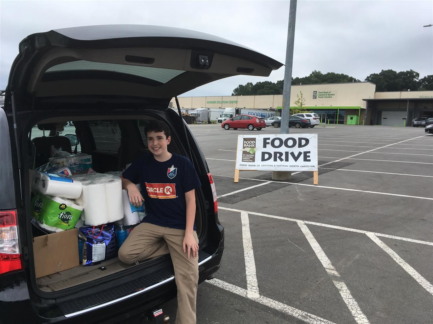 Student by car full of Food Bank goods