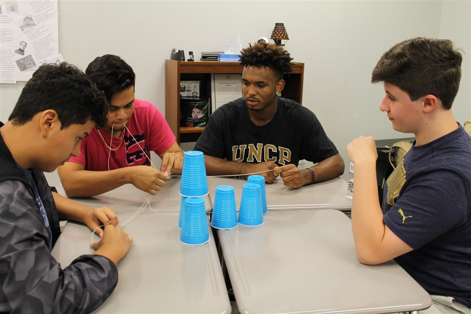 Students participating in string and cup team building activity.