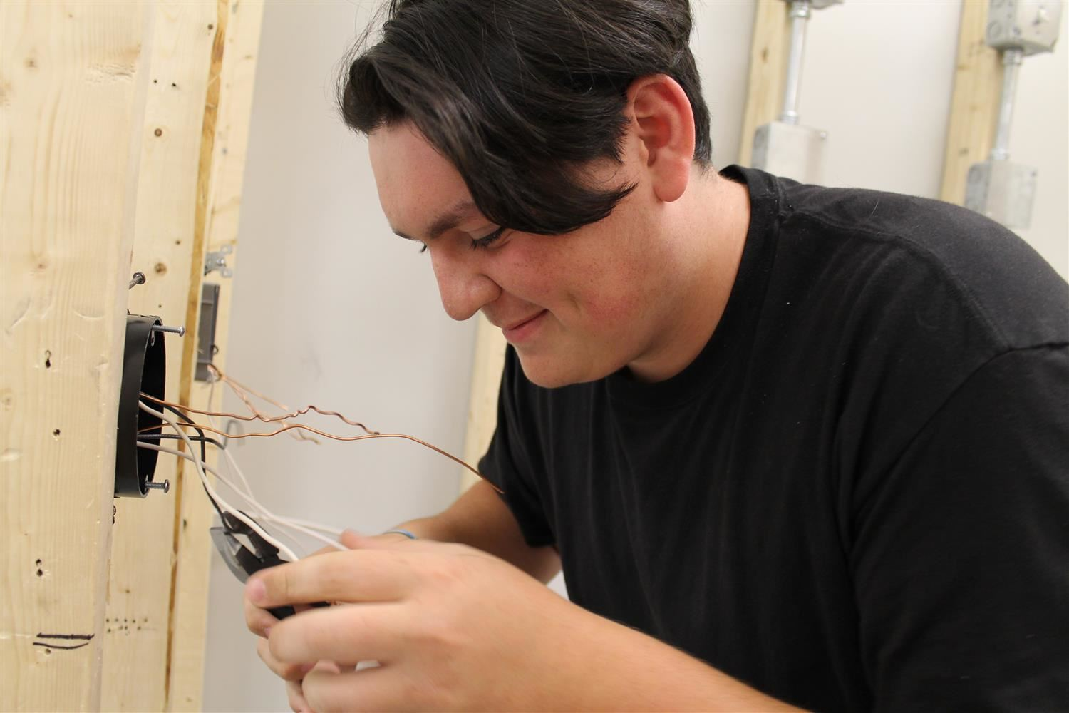 Student wiring an electrical outlet