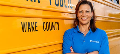 Photo of bus driver in front of a school bus