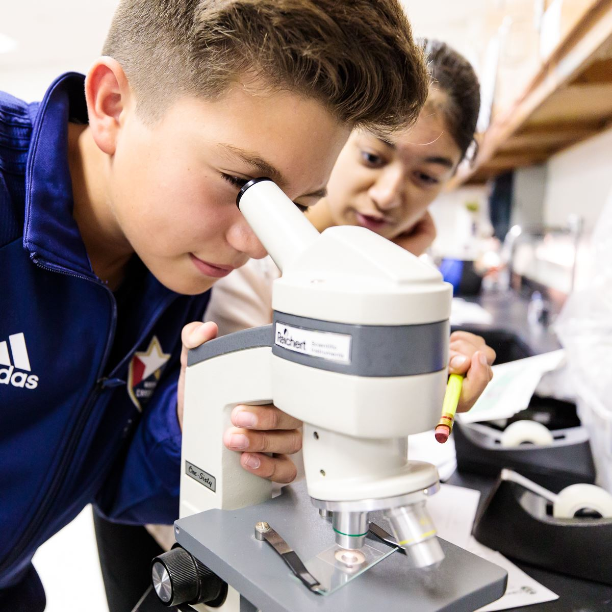 Photo of student with microscope.
