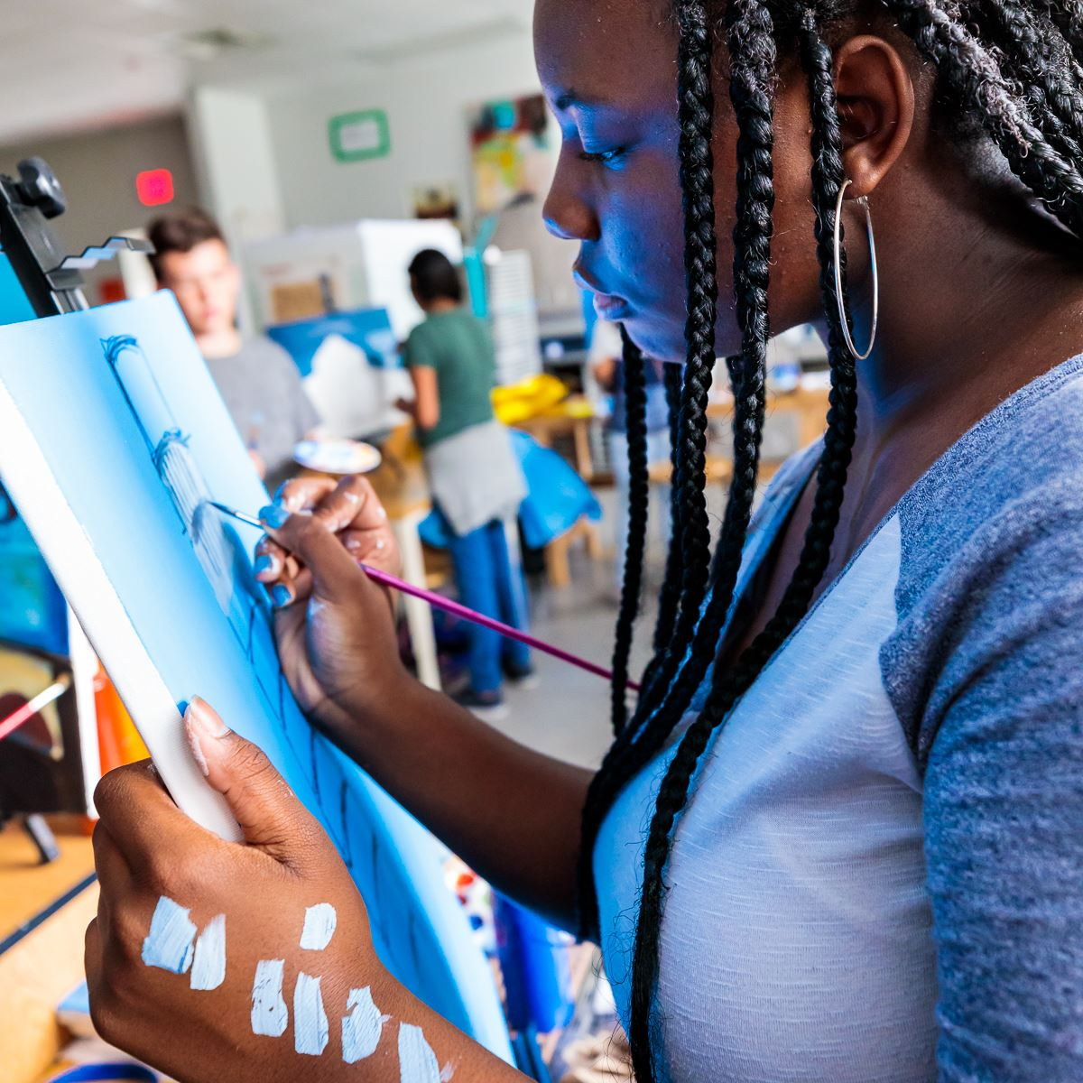 Photo of student artist painting.