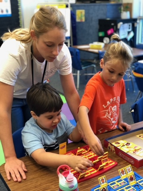Teacher playing a game with 2 students