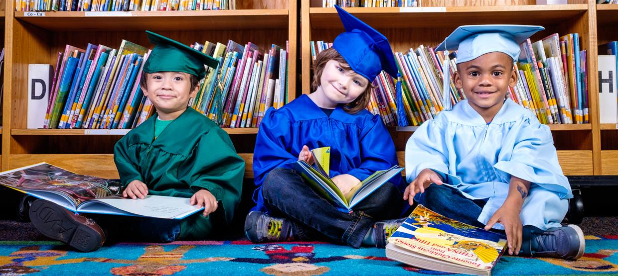 Image of rising Kindergarten students wearing caps and gowns while reading books