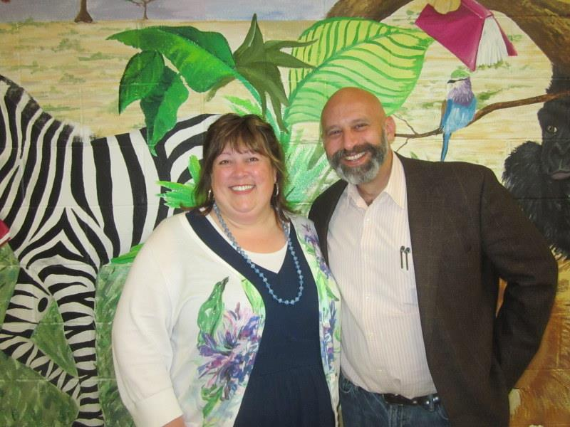Mrs. Lay and Mr. Cohen in front of a zebra mural.