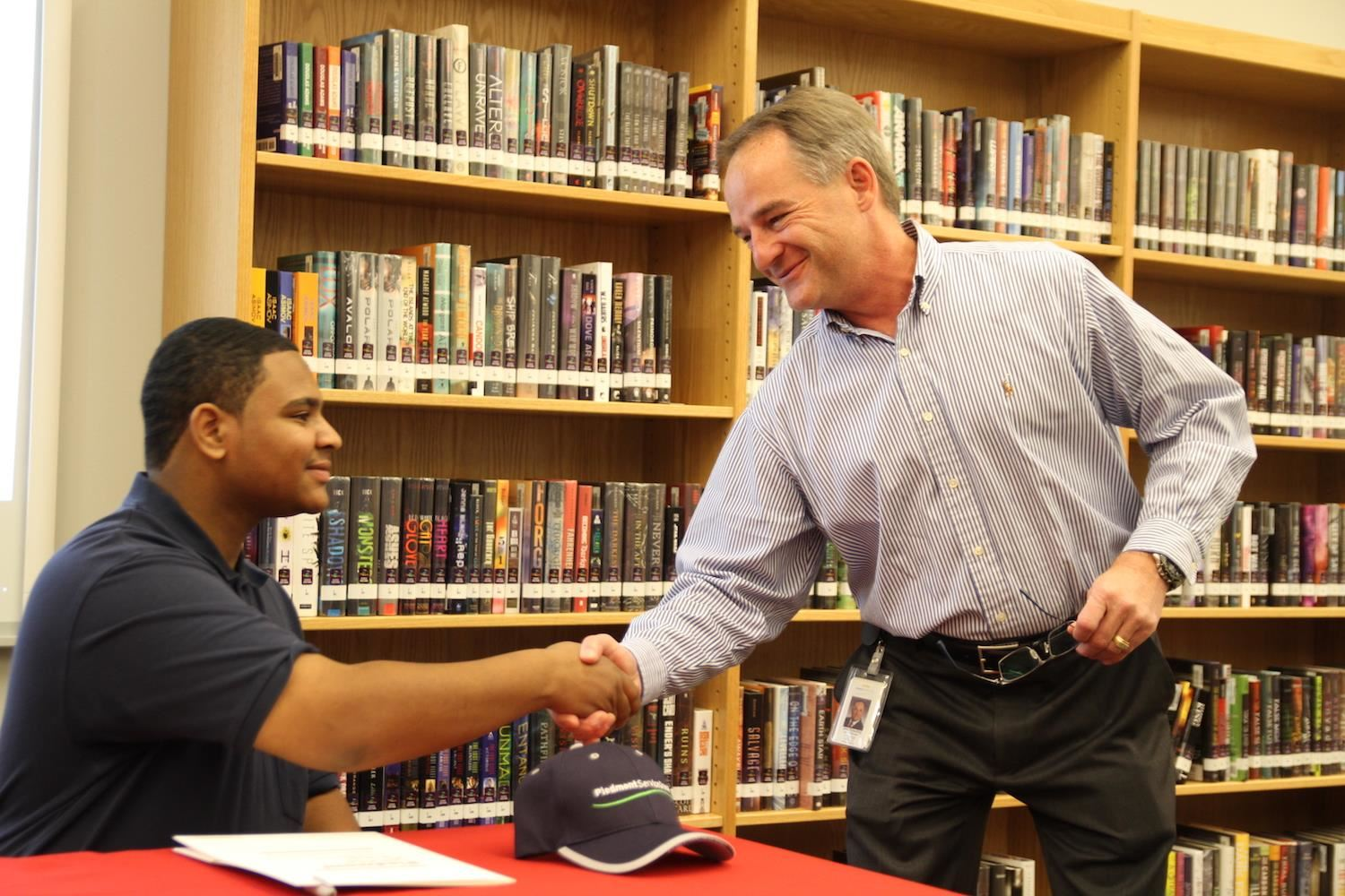 Jerry Spaulding of Piedmont Service Group shakes hands with new hire and Vernon Malone graduate Jordan Mavins.