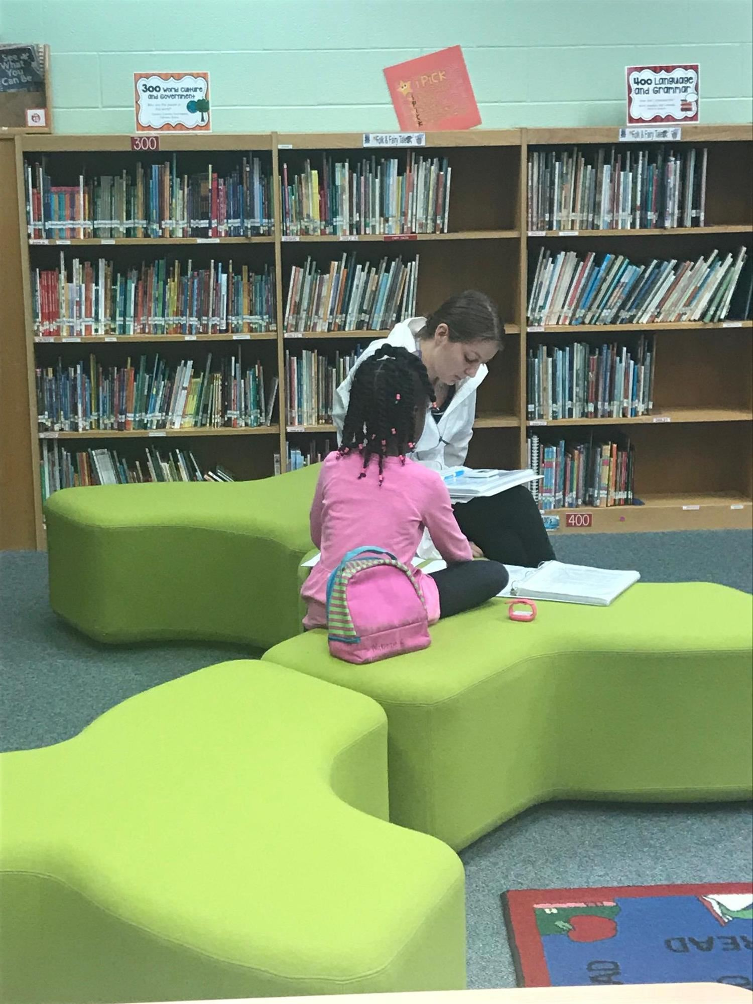 student and teacher reading in the media center
