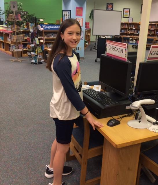 student helping in the media center