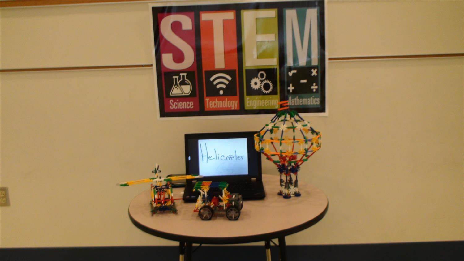 "STEM sign with laptop that reads, ""helicopter"" and three models of vehicles built with K'nex build pieces"